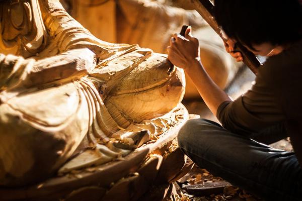 An artisan carving Buddha statue